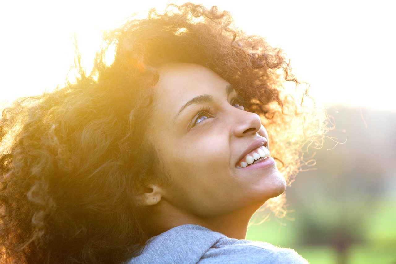 Bigstock-79175111-Young-African-American-Woman-Smiling-And-Looking-Up-e1519144265585